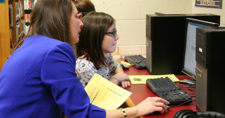 Library Media Specialist Linda Fecura works with student