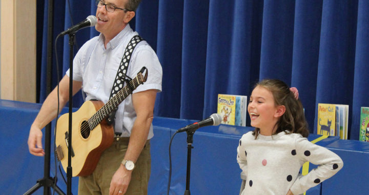 Author Eric Litwin sings with student