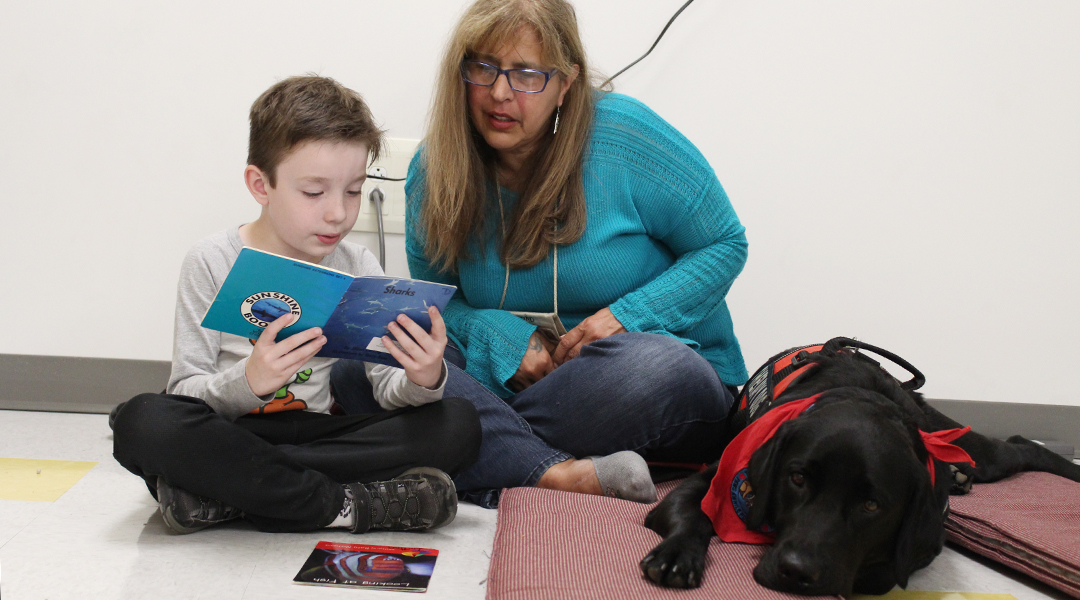Student reads to therapy dog