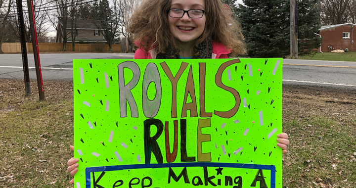 Student with Royals Rule poster